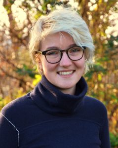 Headshot of Aoife ouside. They are wearing a navy turtleneck and have short blonde hair and glasses.