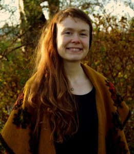 Photo of Olga smiling at the camera. She is outdoors and wearing orange cardigan and has long brown hair.