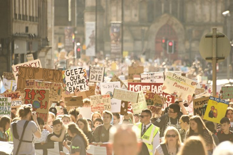 A hazy photo of a large crowd of protesters at a rally organised by climate strikers.