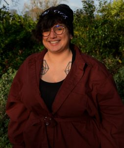 Image of Zoe from the waist up in front of some trees. They are smiling at the camera and wearing a beanie and glasses and a maroon coat.