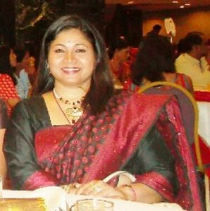 Mala is sitting at a table and smiling at the camera, she is dressed in green and red.