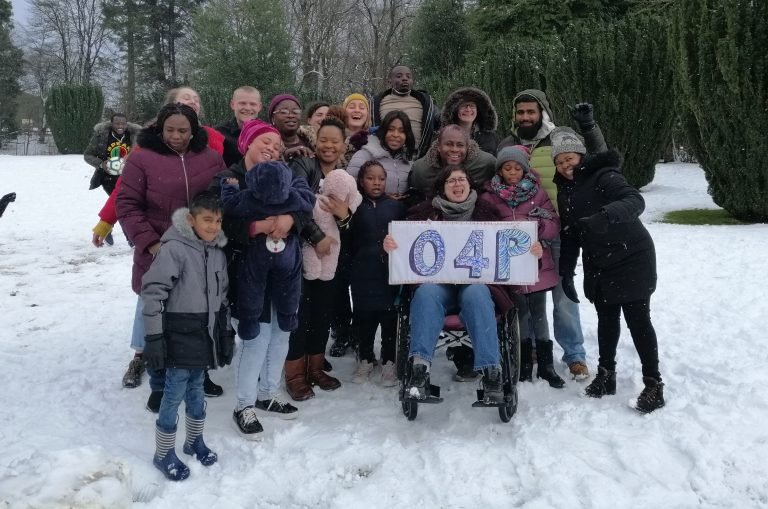 Group of people in the snow and everyone is laughing. Someone is holding a sign that says 'O4P'