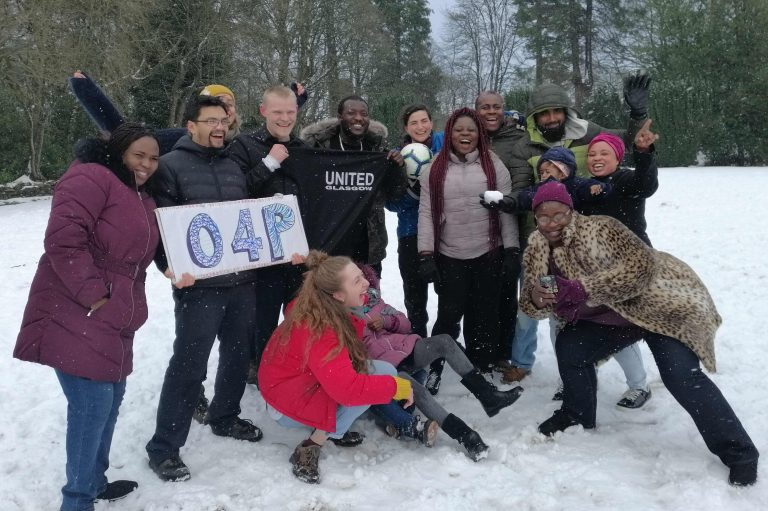 Group of people in the snow, two have fallen over and everyone is laughing. Someone is holding a sign that says 'O4P'