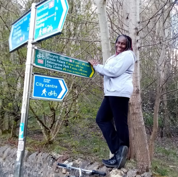 A black woman standing on a wall next to a signpost. She is smiling at the camera with a bike next to the wall