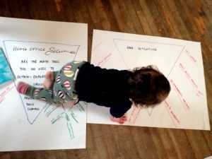 A baby with dark curly hair crawls across flipcharts with writing on them