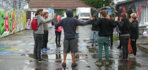 a circle of people are in a wet concrete yard their hands raised at shoulder height