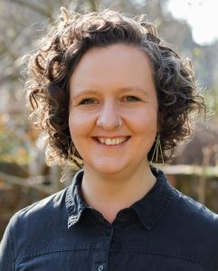 Head shot of Lucy smiling into the camera, she has brown curly hair and is wearing silver earrings and a navy shirt.